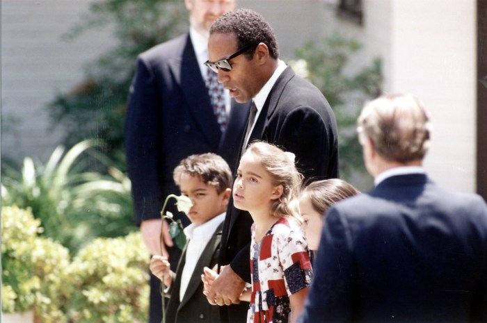 Ex-football player & suspected killer O.J. Simpson (C) w. his children Justin (L) and Sydney (R) at the grave of their murdered mother, Nicole Brown Simpson.